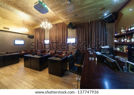 Stylish interior of karaoke bar with leather armchairs and many screens. - stock photo