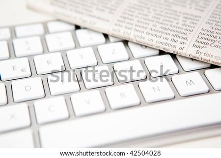 stylish keyboard with newspaper - stock photo