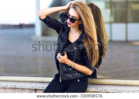 Stylish lady in black posing near mirrored wall, outdoor urban city portrait, glamour blonde model posing at cold autumn rainy day, stylish brutal leather black jacket, sunglasses, makeup. - stock photo