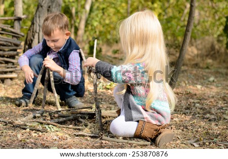 Stylish little boy and girl playing in woodland with sticks happily crouching together on the ground building different structures