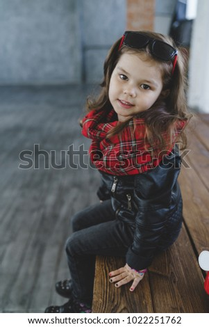 Stylish little girl model sitting on the bench and posing