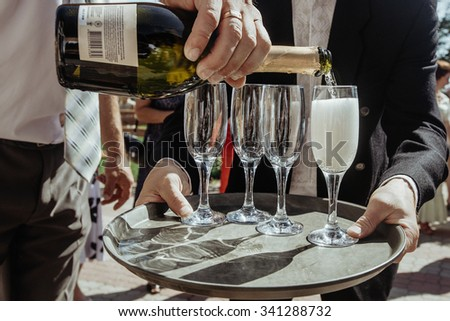 stylish luxury amazing champagne and glasses on a tray, for the celebration of a wedding, catering holiday in the restaurant - stock photo