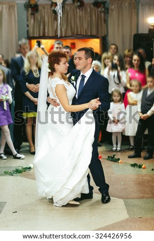stylish luxury happy red haired bride and groom dancing in a restaurant, celebrating wedding