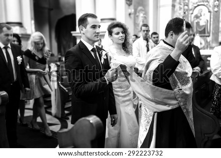 stylish luxury red haired bride and elegant groom, with priest, wedding ceremony in the old church