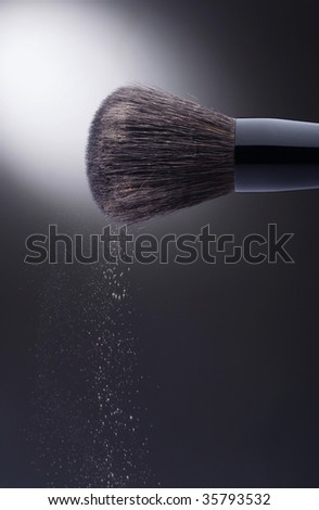 Stylish makeup brush with spilling light rose face powder