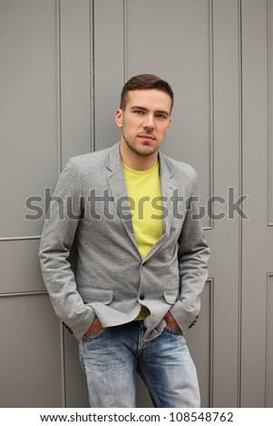 stylish man against grey door - stock photo