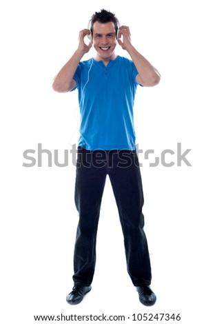 Stylish man enjoying music on headphones, full length shot - stock photo