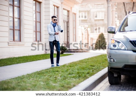 Stylish man goes to his own luxury car disabling protection. Talking on the phone - stock photo