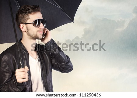 Stylish Man Holding an Umbrella and Talking on His Phone - stock photo