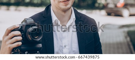 Stylish Man Holding Photo Camera. Professional Holding Video Camera At  Wedding Ceremony, Photographer Or