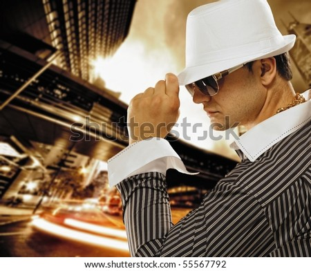 Stylish man in a hat in front of night city
