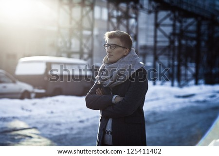 Stylish man in a jacket, sweater, scarf and glasses on the background of the industrial