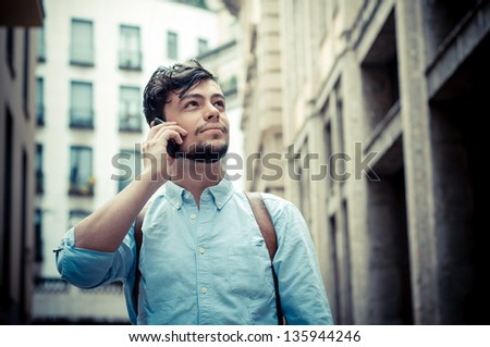 stylish man in the street at the phone in the city - stock photo