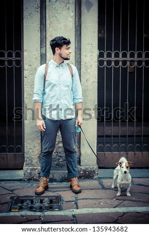 stylish man in the street with a jack russel in front of a wall - stock photo