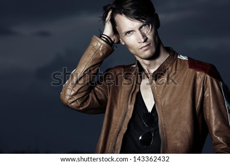 Stylish man on leather jacket against the dark sky - stock photo