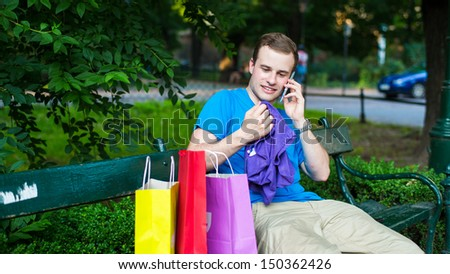 Stylish man on the phone at the park .  He trying a t-shirt - stock photo