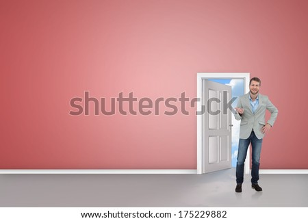 Stylish man smiling and gesturing against door opening showing blue sky
