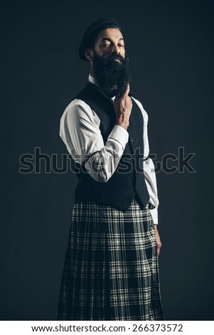 Stylish Man, Wearing Formal Wear Paired with Checkered Skirt, Holding his Long Goatee Beard While Looking at the Camera on Black Background. - stock photo