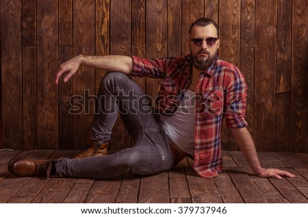 Stylish man with beard in casual shirt and sunglasses looking at camera, sitting on a wooden background - stock photo