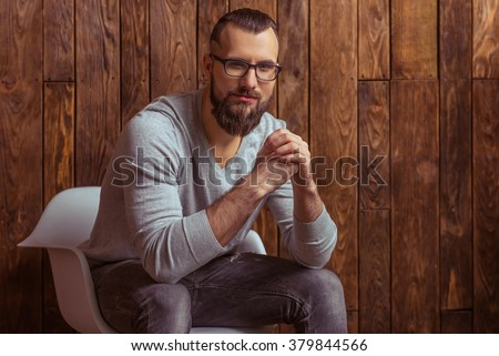 Stylish man with beard in gray sweater and eyeglasses looking at camera and smiling, sitting on a chair against wooden background - stock photo