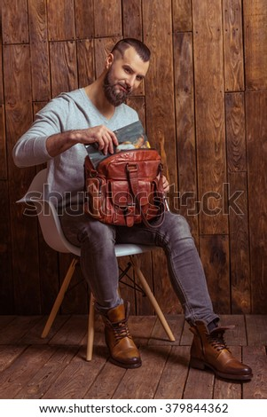 Stylish man with beard in gray sweater putting a magazine into bag and smiling, sitting on a chair against wooden background - stock photo