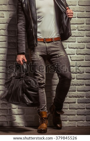 Stylish man with beard in leather jacket holding a black leather bag, standing against brick wall, cropped - stock photo