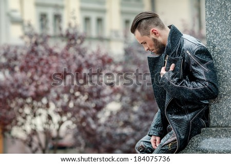 Stylish man with beard standing on the street in a leather coat. Photoshoot men on the street. A man in a fashionable style. Elegant men's hairstyle