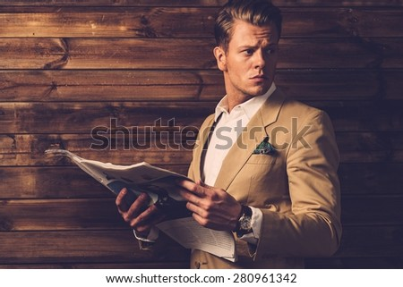 Stylish man with newspaper in rural cottage interior  - stock photo