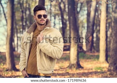 Stylish man with sunglasses posing in autumn park - stock photo