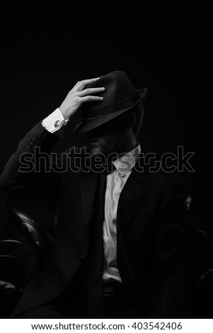 Stylish man with the hat and beard in the chair black and white portrait