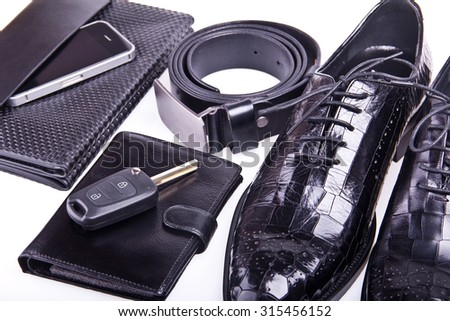 Stylish men's shoes, purse, hand bag, car key, sunglasses, cellphone and black belt on gray background. Crocodile leather. Isolated with shadows.