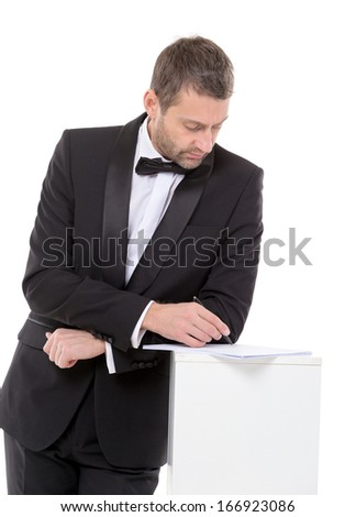 Stylish middle-aged man in a bow tie and suit standing at a pedestal completing a form pausing to read the document with a pen in his hand