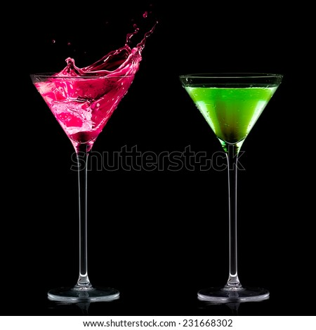 Stylish mini martini glasses with colored fruity cocktails and one splashing out, isolated on black background. Fruity schnapps. - stock photo