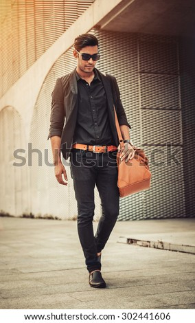 Stylish model looking man in sunglasses with handbag on his shoulder in modern architectural environment. - stock photo