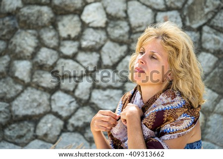 Stylish modern confident attractive blond middle-aged womanin swimwear and scarf on ger shoulders in front of a stone wall blackboard with copyspace - stock photo