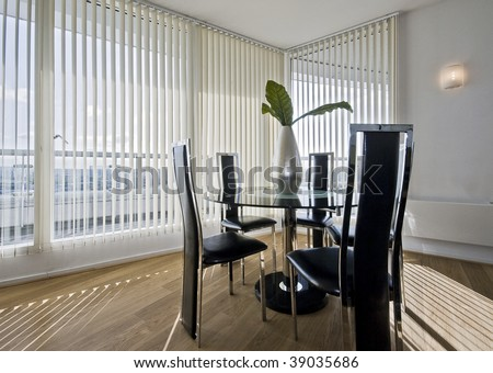 stylish modern dining room with a round glass top table and seats for five - stock photo