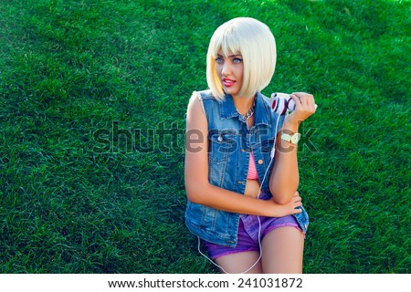 Stylish modern girl sitting on the grass and listening to music on white wig and denim jacket .  - stock photo