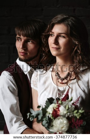 Stylish Newlywed Groom and Bride Standing Together Embraced and Looking Away. Dark Background, Selective Focus on Groom. - stock photo