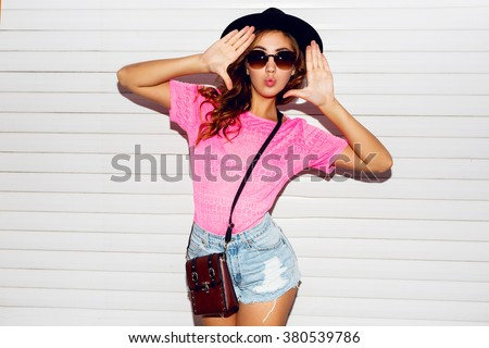 Stylish night flash fashion portrait of trendy  casual young  woman in pink neon  t-shirt , black hat, stylish shirts posing near white urban  wall along .   - stock photo