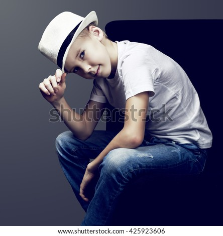 stylish nine years old boy wearing jeans and a hat, isolated against dark studio background