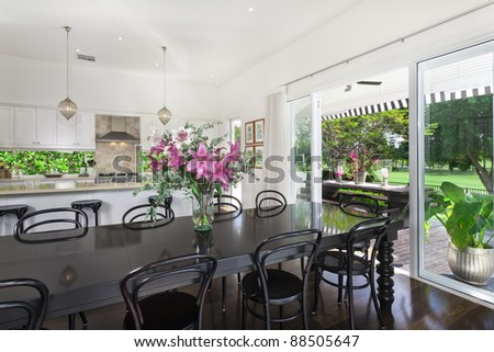 Stylish open plan kitchen with stainless steel appliances and dining area overlooking a pool and golf course - stock photo