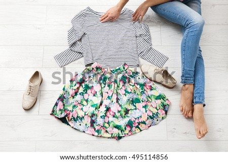 Stylish outfit with female body parts on white wooden floor. Top view and copy space