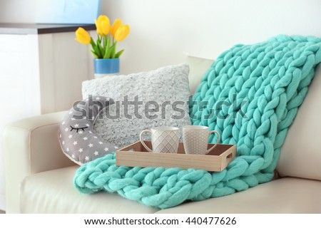 Stylish pillows with turquoise plaid on white couch - stock photo