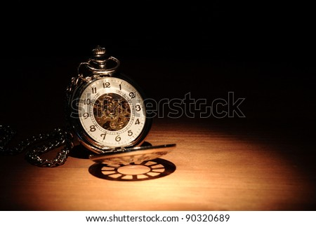 Stylish pocket watch on wooden surface under beam of light - stock photo
