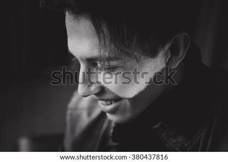 stylish portrait of a young attractive guy with cheekbones  and jacket in the studio posing in bright light in fashionable style sight close-up  with full lips