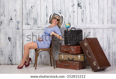 Stylish pregnant lady tourist with suitcases near wooden wall - stock photo