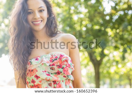 Stylish pretty brunette smiling at camera on a sunny day in the park - stock photo