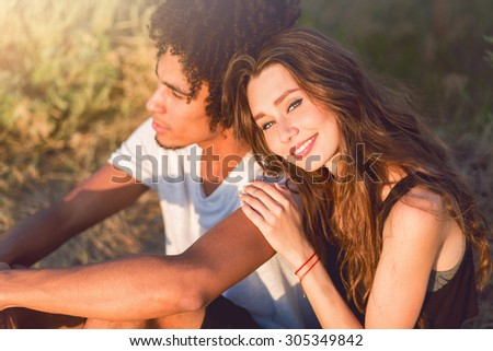 Stylish pretty hipster couple posing  outdoor . wearing trendy sunglasses and autumn outfit . Romantic sunny mood.  Two young people in love sitting in grass and dream . - stock photo