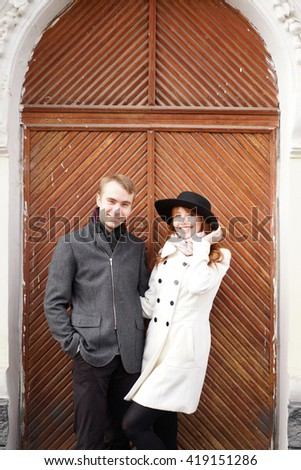 Stylish red-haired woman in black hat with her boyfriend smiling at camera.Wooden doors on background - stock photo