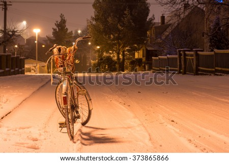 Stylish red sneakers snowy snow in a basket by the vintage bicycle - stock photo